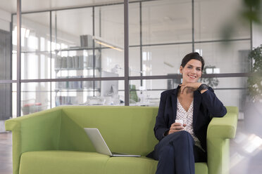 Businesswoman with laptop sitting on a couch and drinking coffee in the office - FKF02700