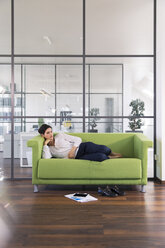 Businesswoman taking a nap lying on a couch in the office - FKF02709