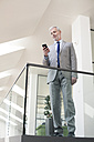 Businessman standing in office using his mobile phone - FKF02721