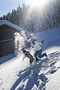 Austria, Altenmarkt-Zauchensee, happy young woman playing with dog in snow - HHF05518