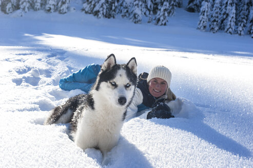 Austria, Altenmarkt-Zauchensee, portrait of smiling young woman lying with dog in snow - HHF05521