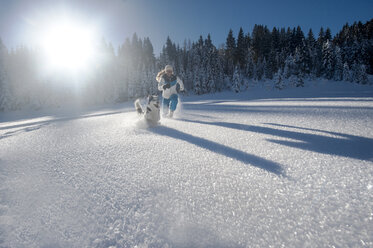 Austria, Altenmarkt-Zauchensee, happy young woman running with dog in snow - HHF05524
