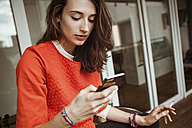 Young woman checking smartphone on balcony smoking a cigarette - FEXF00295