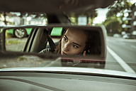 Mirror image of young woman in car talking on the phone - FEXF00301