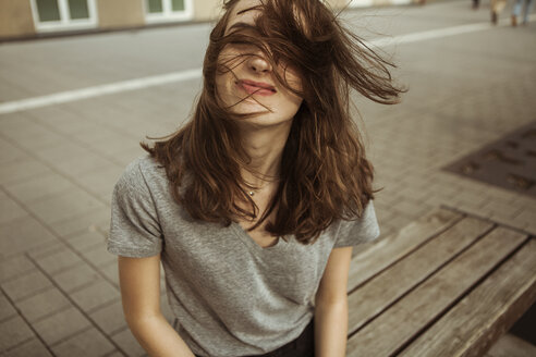 Young woman outdoors with windswept hair - FEXF00304