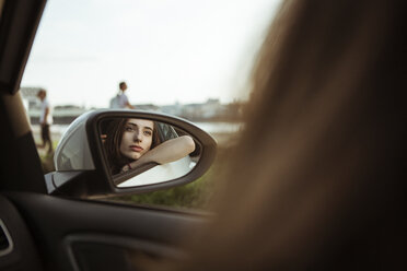Mirror image of young woman in car looking out of window - FEXF00307