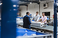 Business people standing on shop floor, discussing product improvement - DIGF02968