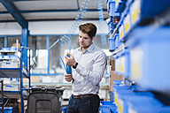 Businessman standing in shop floor, testing products - DIGF02974