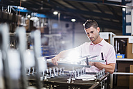 Businessman standing in shop floor, testing products - DIGF02977