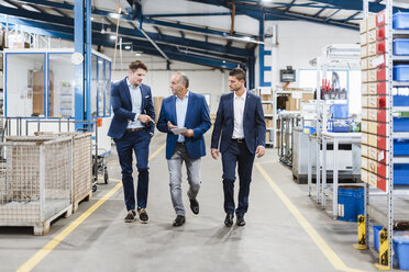 Three businessmen walking through shop floor, discussing decisions - DIGF02989