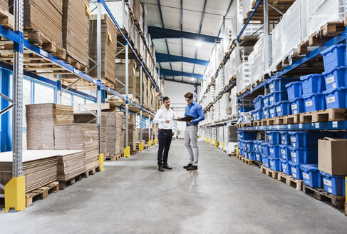 Two businessmen having a meeting in company warehouse - DIGF02991