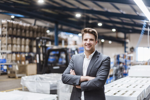 Young manager standing in shop floor, portrait - DIGF03039