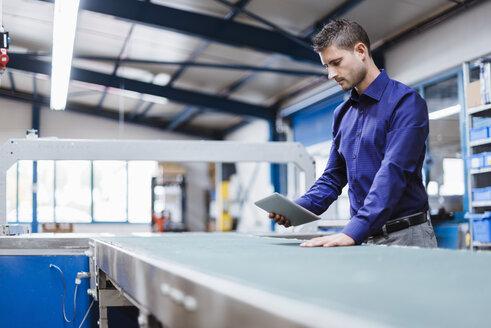 Businessman working in shop floor, using digital tablet - DIGF03042