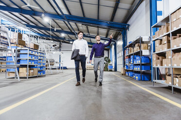 Two businessmen walking through shop floor, talking - DIGF03045