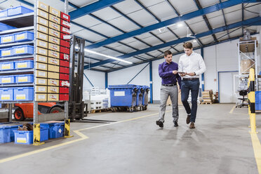 Two business people walking through shop floor. holding digital tablet - DIGF03048