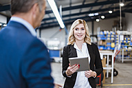 Businesswoman talking to business founder, holding digital tablet - DIGF03063