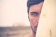 Portrait of young surfer hiding behind surfboard, close-up - SIPF01820