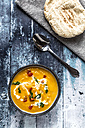 Sweet potato soup in bowl, spoon and bread - SARF03395