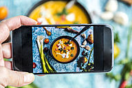 Woman photographing with a smartphone a sweet potato soup - SARF03398