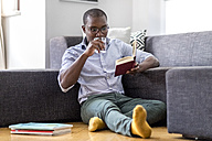 Young man sitting on the floor in the living room reading book and drinking glass of water - MMAF00179