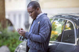 Young man leaning against car using cell phone - MMAF00185