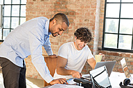 Two young businessmen working together in co-working space, using laptops - SPCF00180