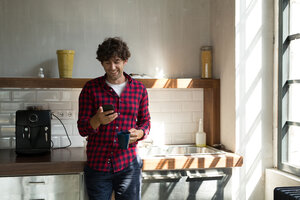 Young entrepreneur standing in company kitchen, drinking coffee, using smartphone - SPCF00222