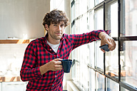 Young entrepreneur standing in company kitchen, drinking coffee - SPCF00225