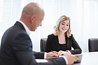 Businessman and businesswoman talking in office - DIGF03087