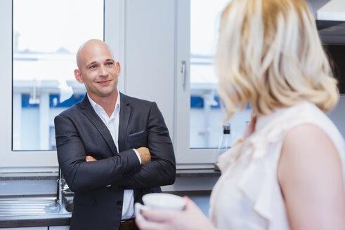 Businessman and businesswoman having coffee break in kitchen - DIGF03096