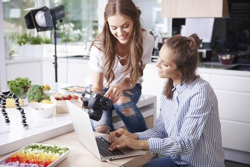 Two food bloggers choosing photos on digital camera - ABIF00034