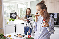 Woman talking on the phone and eating strawberry - ABIF00037