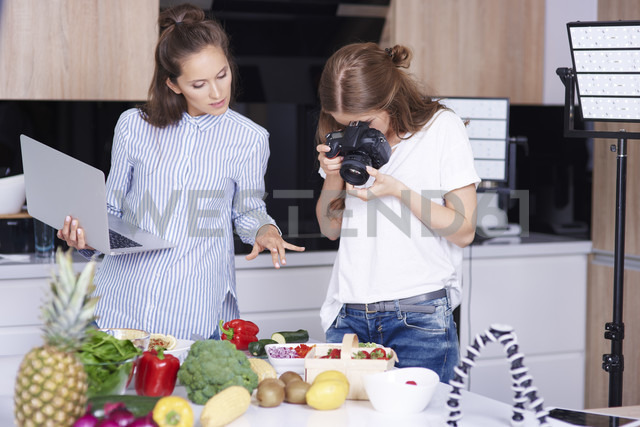 Woman photographing food in kitchen - ABIF00040