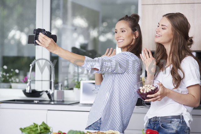 Food bloggers greeting their viewers in kitchen - ABIF00043