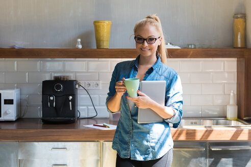 Portrait of smiling businesswoman standing with coffee mug and tablet in the kitchen - SPCF00249
