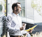 Businessman with papers and coffee to go looking at distance - UUF12061
