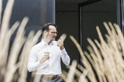 Businessman with coffee to go using cell phone in front of office building - UUF12070