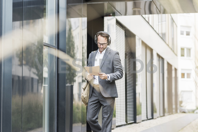 Businessman with headphones reading documents - UUF12079