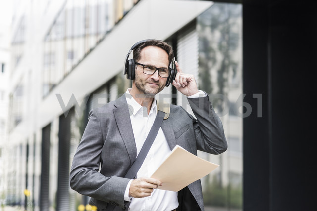 Portrait of smiling businessman with documents and headphones - UUF12082