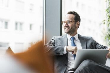 Businessman sitting in lobby using laptop - UUF12097