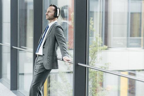 Portrait of businessman with eyes closed listening music with headphones - UUF12100