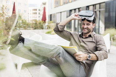 Smiling man with Virtual Reality Glasses and documents sitting on terrace - UUF12106