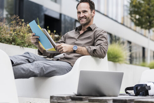 Smiling businessman with document, laptop and Virtual Reality Glasses sitting on terrace - UUF12109