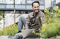 Portrait of smiling businessman working with laptop outdoors - UUF12112