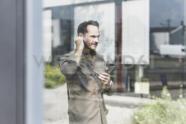 Businessman using smartphone and earphones - UUF12115