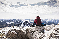 Germany, Bavaria, Oberstdorf, hiker sitting in alpine scenery - UUF12125