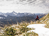 Germany, Bavaria, Oberstdorf, hiker sitting in alpine scenery - UUF12131