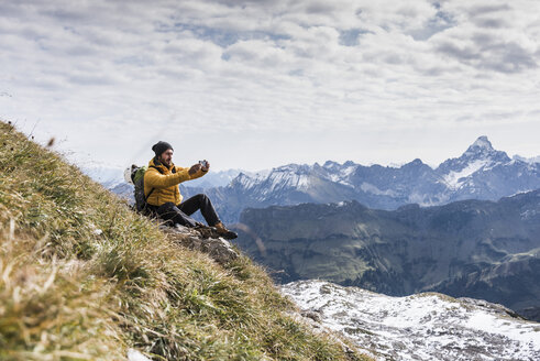 Germany, Bavaria, Oberstdorf, hiker taking picture in alpine scenery - UUF12140