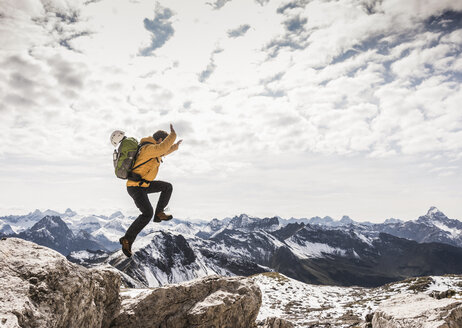 Germany, Bavaria, Oberstdorf, man jumping on rock in alpine scenery - UUF12149
