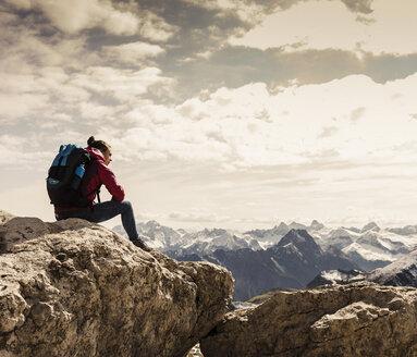 Germany, Bavaria, Oberstdorf, woman sitting on rock in alpine scenery - UUF12152